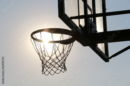 Photo Basketball hoop on basketball court under syn