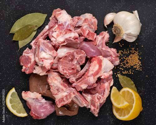 Fresh raw goat meat stew like cuts on black cutting board with spices mustard seeds, garlic, lemon, and bay leaves.