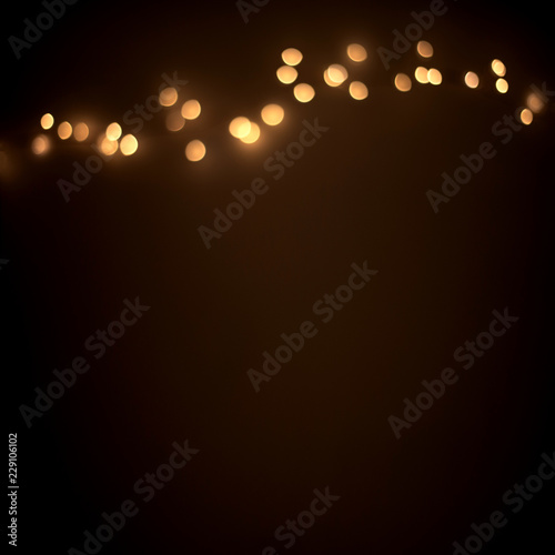 Defocused golden christmas lights on  dark abstract background.  Glowing light bulb garland, copy space Wall mural