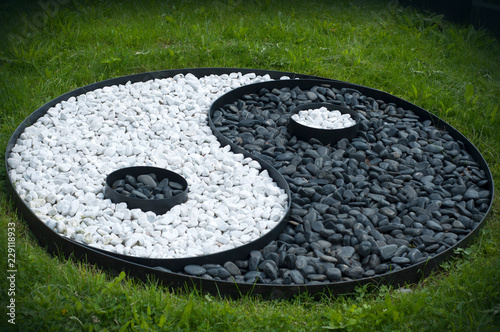 Photo  Sign of yin yang laid out of black and white stones on a green lawn