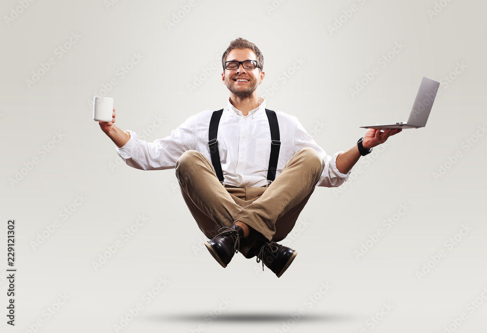 Fototapety, obrazy: Young man is soaring in the air with a Cup of coffee and a laptop