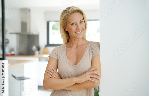 40-year-old blond woman standing inside house Fototapeta