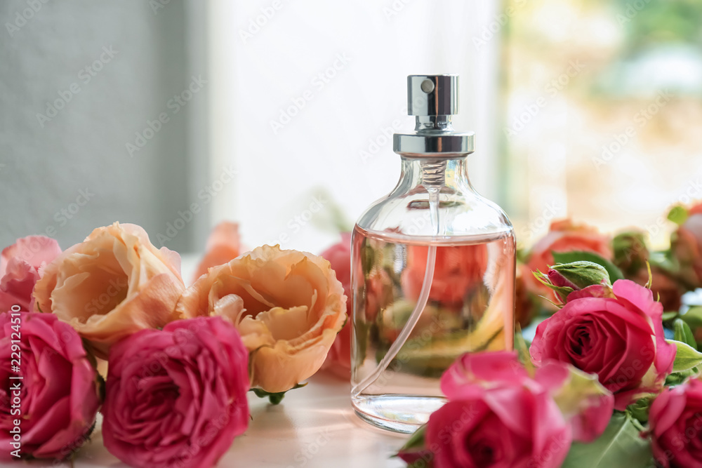 Fototapety, obrazy: Bottle of perfume with beautiful flowers on white table