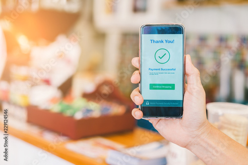 Valokuva  Hand holding smartphone showing payment successful transaction at department sto