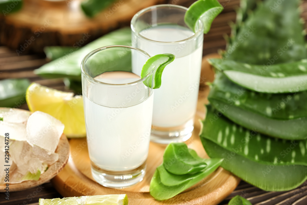 Fototapeta Glasses of aloe vera juice on wooden board