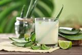Glass of aloe vera juice on wooden table