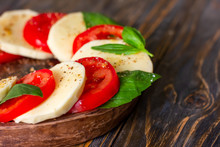 Caprese Salad With Mozzarella On A Light Wooden Background, Close Up