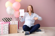 Beautiful Pregnant Woman With Baby Shower Gifts Near Color Wall