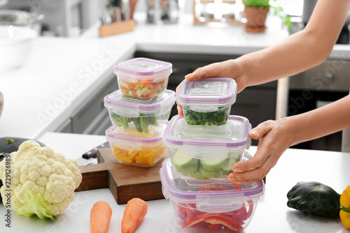 Obraz na plátně Woman holding stack of plastic containers with fresh vegetables for freezing at