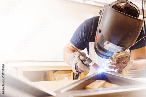 Male in face mask welds with argon-arc welding Canvas Print