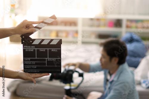 Vászonkép Hand holding clapper board on blurred movie director