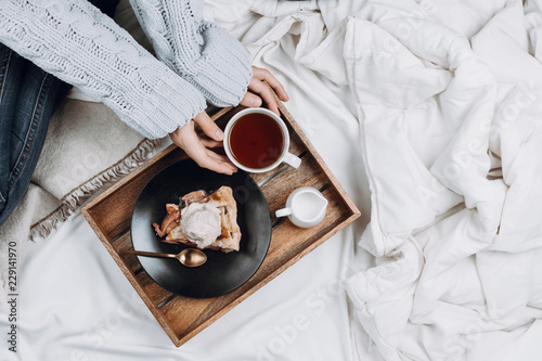 Fotografía  Cozy flatlay of bed with wooden tray with pie, ice cream and black tea and woman