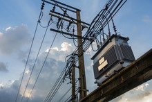 Electrical Transformer, High Voltage Power Transformer In Town With Sky On Evening Background