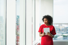 A Woman With Tablet Standing By The Window Against London Panorama.