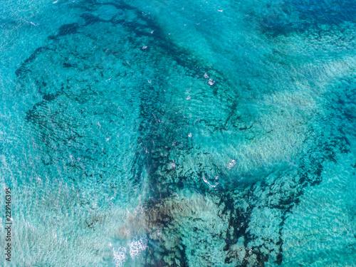 Fotografie, Obraz  Vista aerea di un mare cristallino con onde e surfisti
