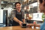 Waiter serving coffee to customer