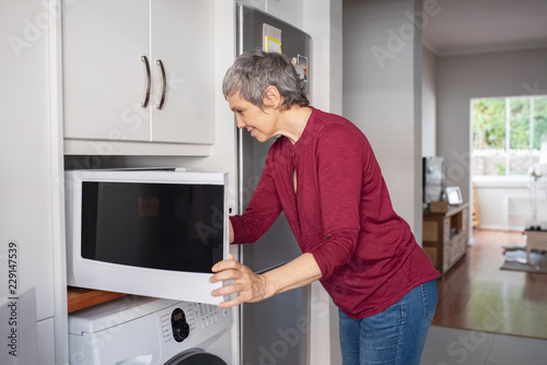 Mature woman using microwave oven
