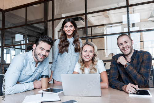 happy young business colleagues working with gadgets and smiling at camera in office