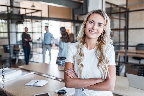Fotografía  beautiful young businesswoman standing with crossed arms and smiling at camera i