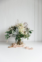A Wedding Bouquet In Soft Green, Beige And Pink Tones In A White Neutral Setting Waiting For The Bride On Her Special Day.