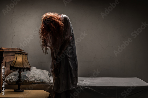 Fotografiet Scary woman possessed by devil in the bed. Exorcism of priest.