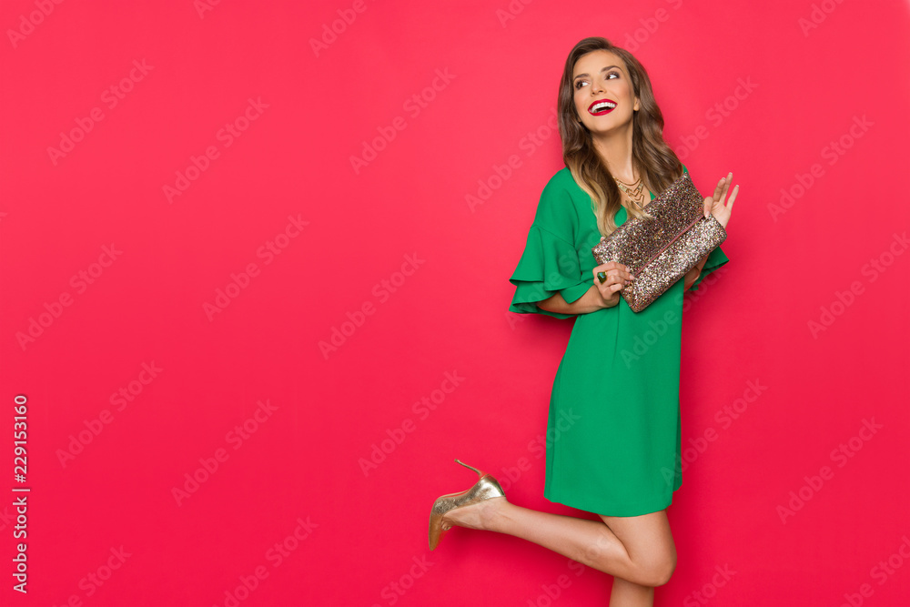 Fototapety, obrazy: Happy Beautiful Young Woman In Green Mini Dress Is Holding Gold Clutch And Looking Away