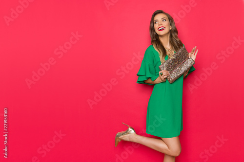 Fotografía  Happy Beautiful Young Woman In Green Mini Dress Is Holding Gold Clutch And Looki