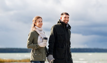 Love, Relationship And People Concept - Smiling Couple With Tumbler Walking Along Autumn Beach And Holding Hands