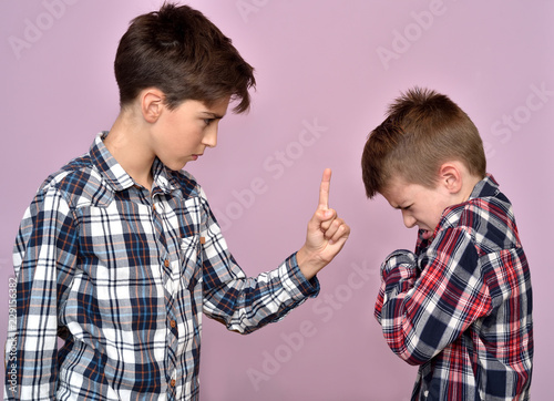 Angry young boy with index fingers up scolding a scared little brother Wallpaper Mural
