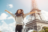 Fototapeta Wieża Eiffla - Young attractive happy woman jumping for joy against Eiffel Tower in Paris, France. Portrait of travel tourist girl on vacation walking happy outdoors. Gorgeous mixed race Asian Caucasian female