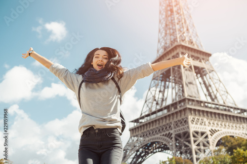 Photo Young attractive happy woman jumping for joy against Eiffel Tower in Paris, France