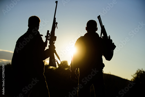 Foto op Canvas Jacht Hunters friends gamekeepers with guns silhouette sky background. Hunters rifles nature environment. Hunter friend enjoy leisure. Hunting with partner provide greater measure safety fun and rewarding