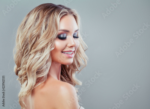 Poster de jardin Salon de coiffure Smiling blonde woman with healthy wavy hair and makeup on blue background