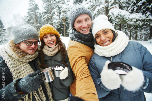 фотографія  Positive excited young multi-ethnic friends in warm clothing holding thermos mug
