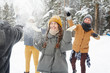 canvas print picture - Happy young friends in winter coats having snowball fight in forest: excited girl standing in center and feeling snow on face