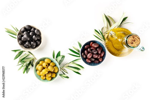 Overhead photo of various olives in bowls and a cruet of olive oil, shot from the top on a white background with copy space