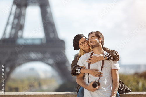 Paris Eiffel tower romantic tourist couple embracing kissing in front of Eiffel Tower, Paris, France. Dating couple posing in casual trendy clothes near outdoor. Handsome man with camera and cute