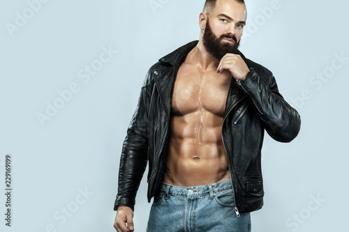 Close-up portrait of a brutal bearded man topless in a leather jacket Tablou Canvas