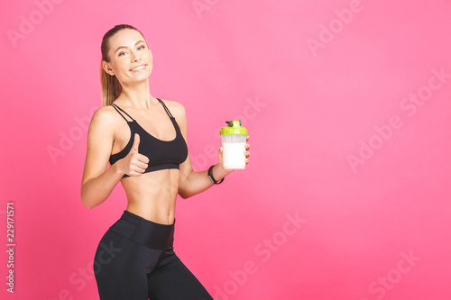 Fotografia  Athletic young woman with protein shake bottle