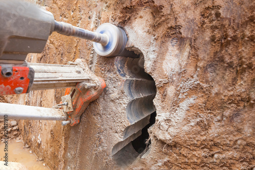 Obraz drilling a hole in a concrete wall with a professional tool with a diamond wheel - fototapety do salonu