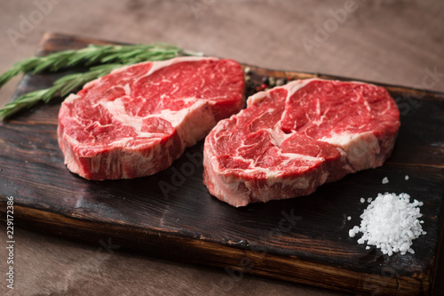 Poster Steakhouse Two fresh raw rib-eye steak on wooden Board on wooden background with salt, pepper and rosmary in a rustic style