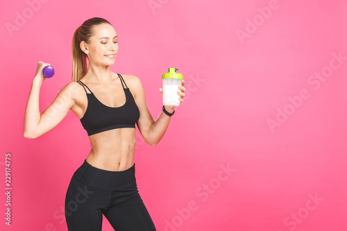Fotografia Portrait of athletic young woman with protein shake bottle and dumbells