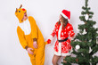 Christmas, holidays and joke concept - Funny woman in santa suit and man in deer costume fooling around near christmas tree on white background