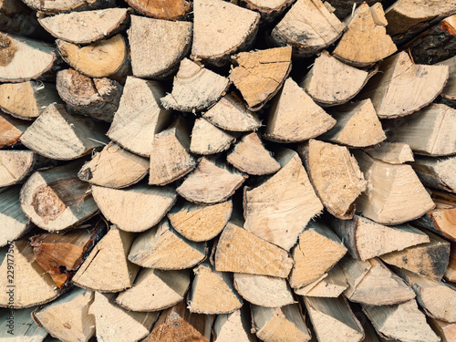 Chopped aspen firewood stacked in woodpile, texture