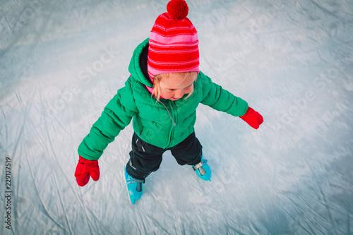 happy little girl learning to skate in winter