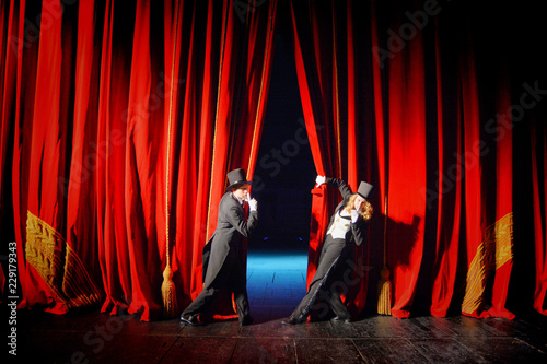 Fotografie, Obraz  Actor in a tuxedo and hat looks behind the theater curtain