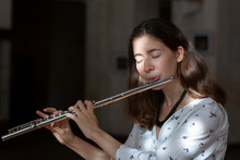A Beautiful Woman Posing While Playing On A Flute