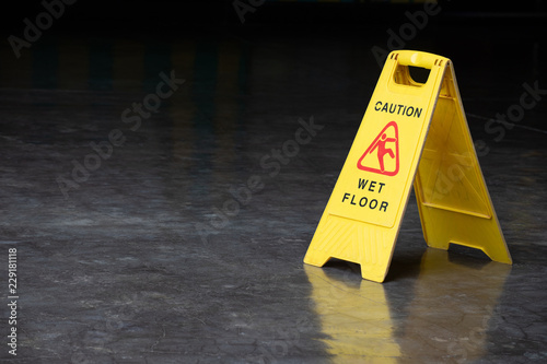 Fotografia  wet floor sign on cement ground. yellow plastic warning sign.