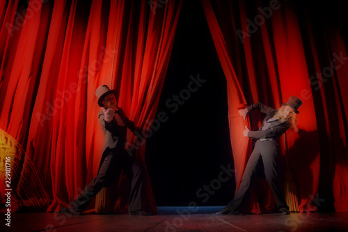 Actor and actress in tuxedos close the theater curtain