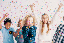 Happy Multicultural Group Of Kids Having Fun During Birthday Party With Confetti